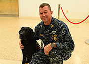 Lovell FHCC Command Master Chief poses with a therapy dog.