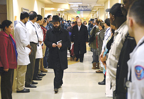 The Argiewicz family's rabbi, Tzali Wilschanski, and the funeral director walk with the morgue cart as civilian employees and Sailors pay their respect during the Final Salute.