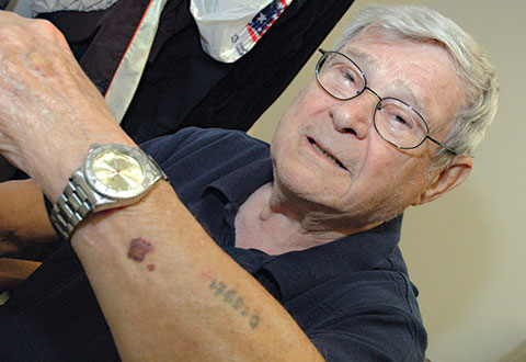 Korean War Air Force Veteran Paul Argiewicz shows the tattoo from his imprisonment in Nazi camps during World War II.