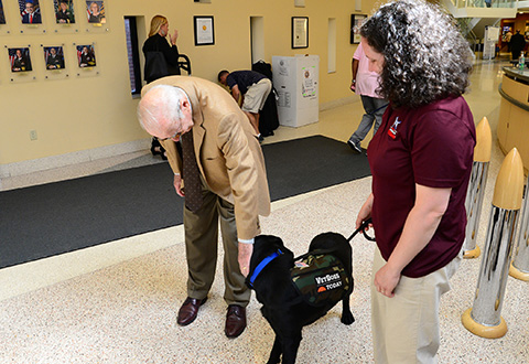 James A. Lovell pets a therapy dog