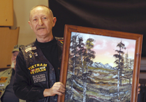 Richard Beauvais holds up the painting he recently gave to a fellow Veteran during a United States Veterans Arts Program event at Lovell FHCC this spring. Every week at the Expressive Arts therapy meeting, Beauvais starts and finishes a painting and donates it to a combat Veteran.