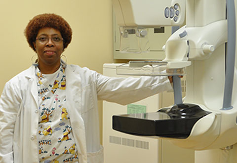 A staff member standing next to a mamography machine